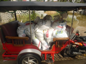 Rice and tarpaulins are put into a tuk tuk